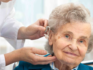 elderly women having hearing aid checked