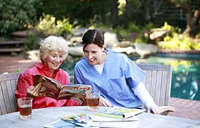 Caregiver and Senior Client Outside Reading